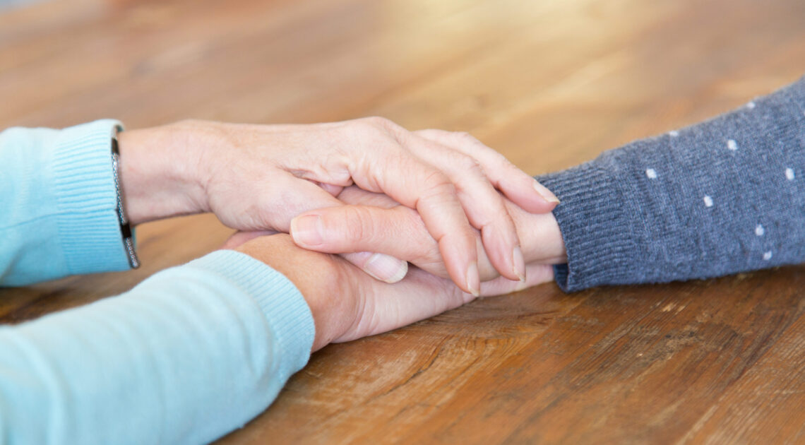 Closeup of senior woman holding daughters hand. Family members helping each other in difficult times. Taking care concept